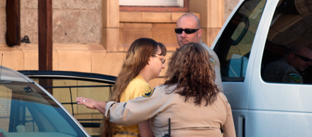 Joanna Beckett McElrath is escorted into court at her first court appearance in 2012.