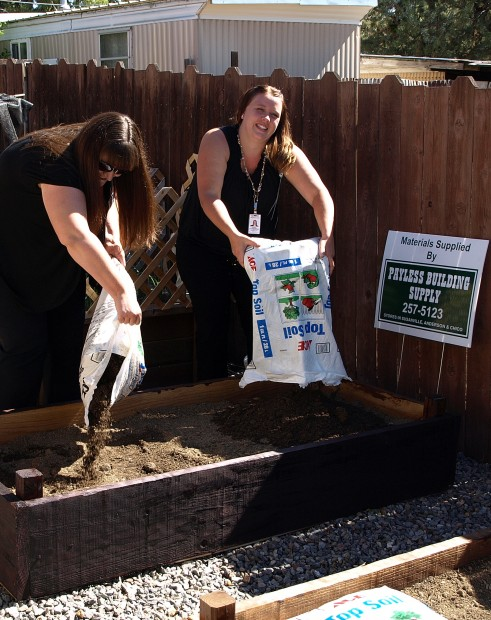 Eskaton's Social Services Coordinator Charlotte Roberts and Emily Griffin, Lassen Public Health's SNAP Educator finish filling up one of the raised beds with potting soil