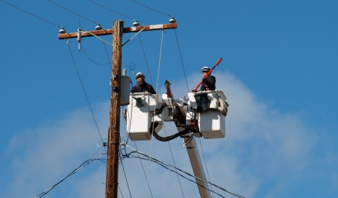 Linemen Neil Dockery (on the left) and Adam Hull work to repair a power pole at the corner of Mill and South Pine Streets.