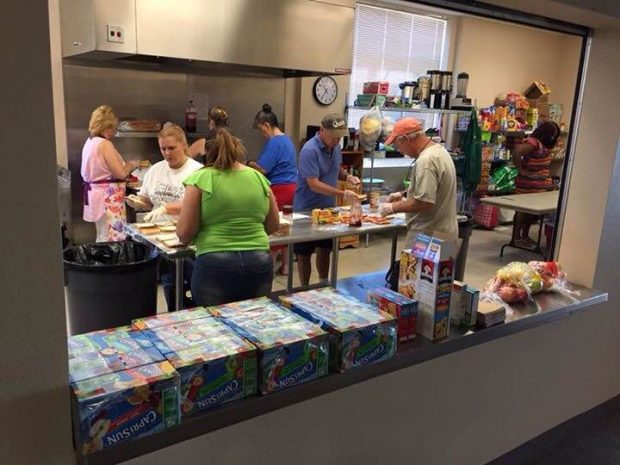 A group of hard working volunteers preparing lunches for the CEFC's free summer lunch program. ~photo provided